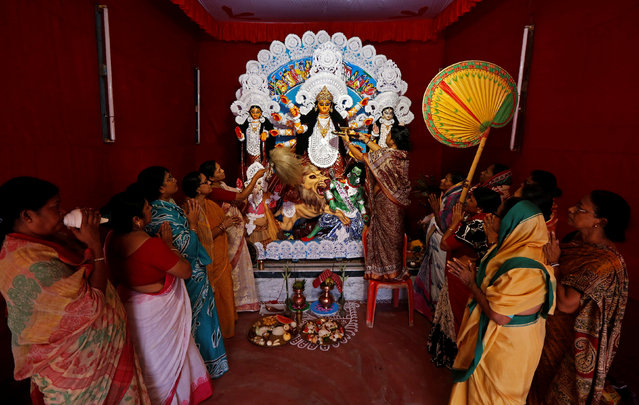 Women offer prayers in front of an idol of Hindu goddess Durga, inside a home, ahead of the Durga Puja festival in Kolkata, India September 26, 2017. (Photo by Rupak De Chowdhuri/Reuters)
