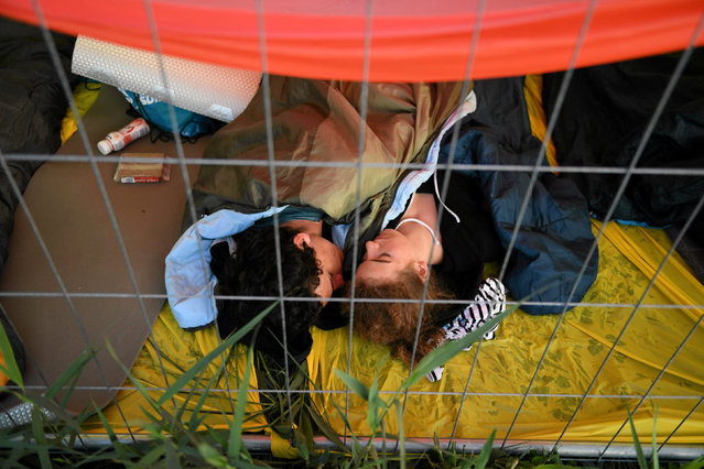 Pilgrims rest behind a fence at the Campus Misericordiae during World Youth Day in Brzegi near Krakow, Poland, July 31, 2016. (Photo by Lukasz Krajewski/Reuters/Agencja Gazeta)