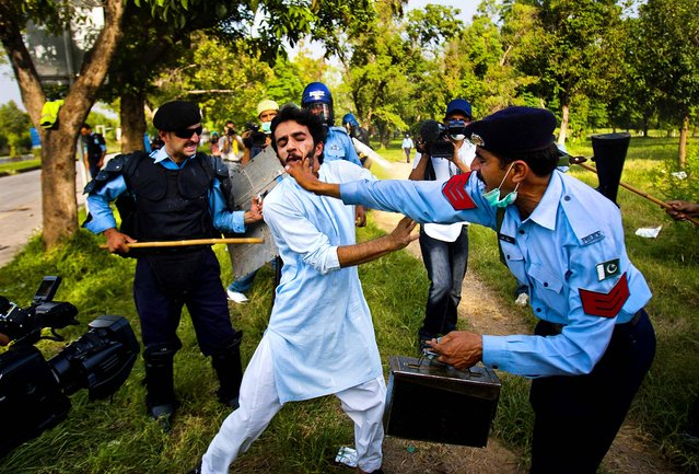 Police officers beat a protestor who tried to approach the U.S. embassy,  in Islamabad, Pakistan, on September 21, 2012. Demonstrations turned violent and scores of people were killed died after police opened fire on rioters torching a cinema in the northwest city of Peshawar (Photo by Anjum Naveed/Associated Press)