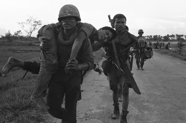A wounded Cambodian trooper grimaces in pain as a buddy carries him to a medic station on RTE 5, an embattled highway northwest of Phnom Penh, Cambodia on July 6, 1973. Government forces engaged entrenched Khmer rebels about 40 miles from the Cambodian capital. (Photo by Chhor Yuthy/AP Photo)