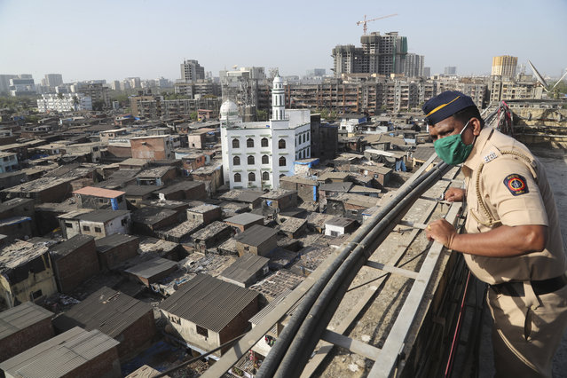 In this April 9, 2020 file photo, an Indian police officer keeps watch from atop a building over Dharavi, one of Asia's largest slums, during lockdown to prevent the spread of the new coronavirus in Mumbai, India. As Indians await details of a huge coronavirus relief package Prime Minister Narendra Modi has announced to jump-start the economy, the virus outbreak in the financial capital of Mumbai and elsewhere in Maharashtra state is starting to overwhelm hospitals, prisons and slums, complicating any economic recovery plan. (Photo by Rafiq Maqbool/AP Photo/File)