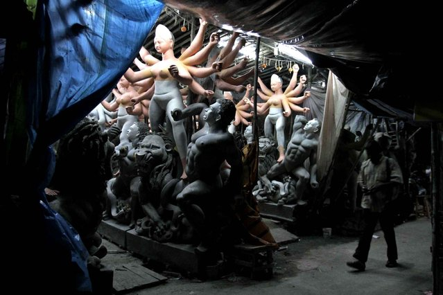 People walk past idols of Hindu goddess Durga being prepared ahead of the Durga Puja festival at Kumartuli or potters' place in Kolkata, India, Wednesday, September 17, 2014. The festival is scheduled to begin Sept. 30. (Photo by Bikas Das/AP Photo)