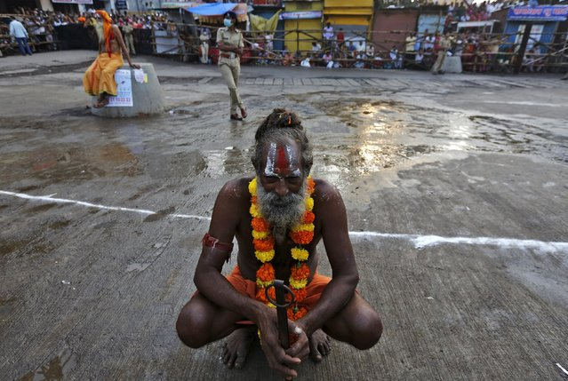 "A sadhu or a Hindu holy man waits to take dip in the waters of Godavari river during the second ""Shahi Snan"" (grand bath) at Kumbh Mela or Pitcher Festival in Nashik, India, September 13, 2015. (Photo by Adnan Abidi/Reuters)"