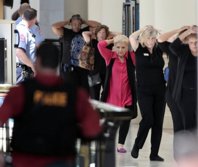 Mall workers and visitors exit to safety through the upper floor food court at Crabtree Valley Mall with hands on their heads as the mall is evacuated in Raleigh, N.C., Saturday, August 13, 2016. Raleigh's police chief says investigators are still trying to determine whether there was a shooting at the Raleigh mall where witnesses reported hearing gunfire. (Photo by Harry Lynch/The News & Observer via AP Photo)