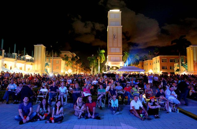 People watch the debate on a large screen at Mizner Park in Boca Raton. (Photo by Allen Eyestone/The Palm Beach Post)