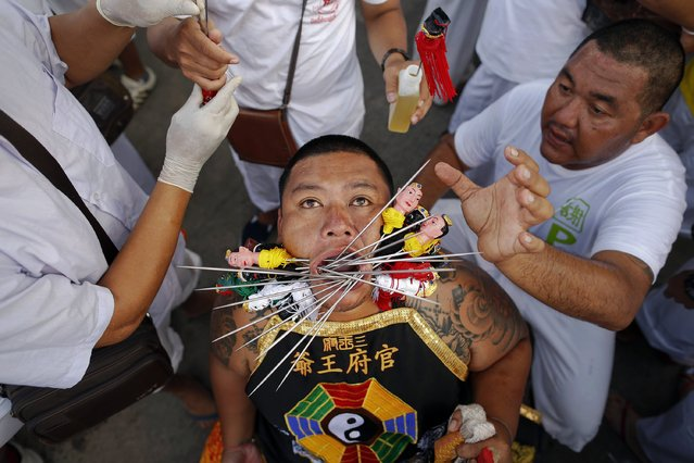 A devotee of the Chinese Bang Neow Shrine is helped to put more spikes through his cheeks before a procession celebrating the annual vegetarian festival in Phuket September 29, 2014. (Photo by Damir Sagolj/Reuters)