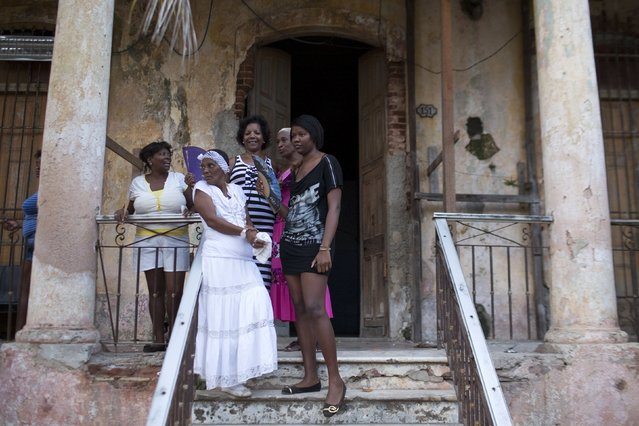 People talk during the party of Yensy Villarreal, 9, (not pictured), in celebration for becoming a Santero after passing a year-long rite of passage in the Afro-Cuban religion Santeria, Havana, July 5, 2015. (Photo by Alexandre Meneghini/Reuters)