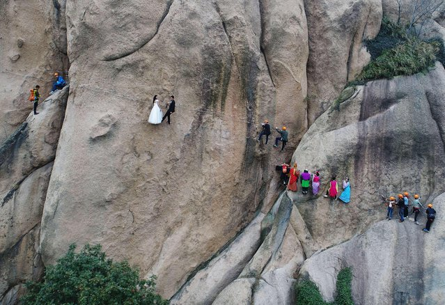 "A newlywed couple dangling from a cliff face poses for wedding photos at the Chaya Mountain scenic spot on November 11, 2017 in Zhumadian, Henan Province of China. Chaya Mountain scenic spot was the shooting place for TV series ""Journey to the West"" and working staff dressed as main characters in this TV series to send the blessing to the newly-weds. (Photo by VCG/VCG via Getty Images)"