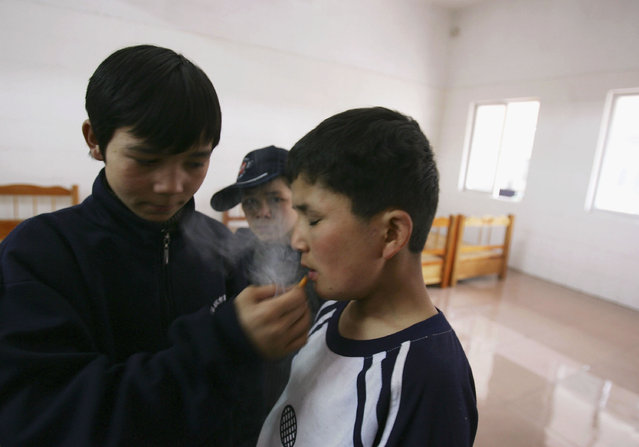 Maimaiti Aili (R), a 13-year old boy from China's Xinjiang Uygur Autonomous Region, smokes at an assistance center February 24, 2005 in Shenzhen, Guangdong Province, China. (Photo by Cancan Chu/Getty Images)