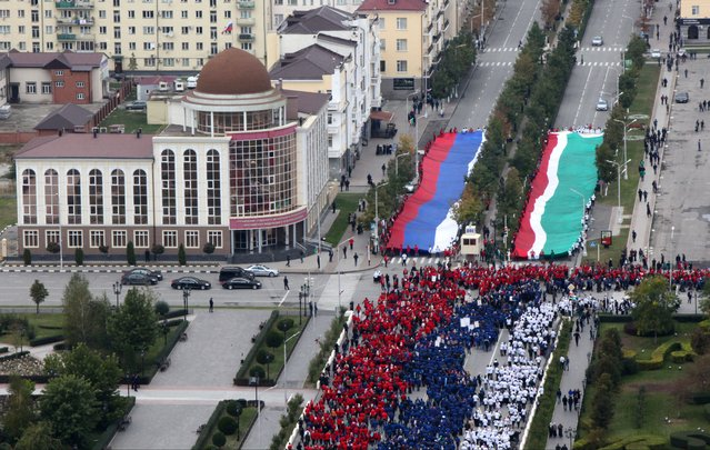 People dressed in colors of the Russian flag pass giant Russian and Chechen flags to gather for a rally in central Grozny, Russia, Tuesday, October 7, 2014. (Photo by Musa Sadulayev/AP Photo)