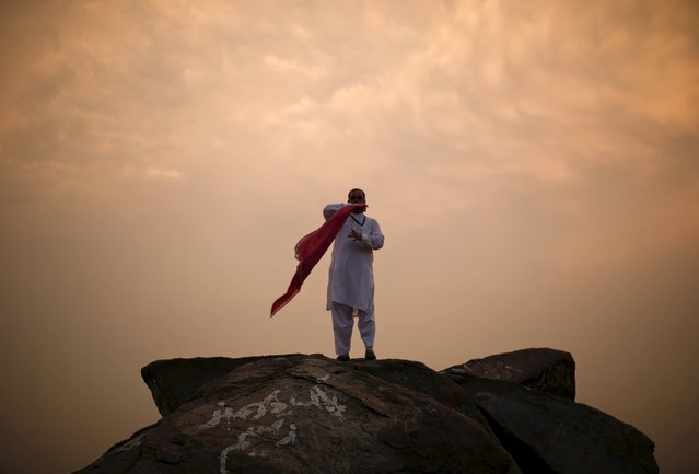 A Muslim pilgrim prepares his scarf as he stands atop Mount Thor in the holy city of Mecca ahead of the annual haj pilgrimage September 19, 2015. (Photo by Ahmad Masood/Reuters)