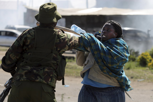 A woman struggles with a policeman as police try to stop the opposition from holding demonstrations in Nairobi, Kenya, Tuesday, November 28, 2017. (Photo by Brian Inganga/AP Photo)