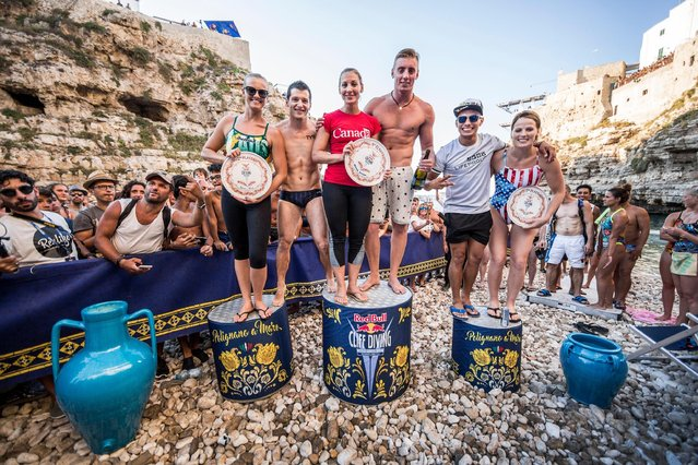 (L-R) Rhiannan Iffland of Australia, Steven LoBue of the USA, Lysanne Richard of Canada, Artem Silchenko of Russia, Jonathan Paredes of Mexico and Rachelle Simpson of the USA celebrate on the podium during the fifth stop of the Red Bull Cliff Diving World Series in Polignano a Mare, Italy on August 28, 2016. (Photo by Dean Treml/ANSA/Red Bull Press Office)