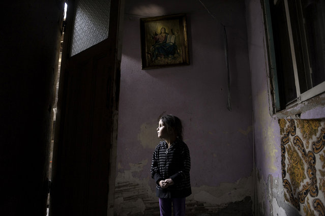 Four-year-old Ana-Maria Tudor, above, stands in the light of her doorway in Bucharest, Romania, hoping for a miracle as her family faces eviction from the only home they have ever had. Her father recently had a gall bladder surgery that resulted in an infection and left him unable to work. The one room they live in has no bathroom or running water. (Photo by Renée C. Byer/Living on a Dollar a Day)