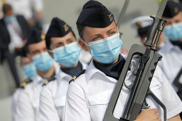 Soldier wear face masks prior to the Bastille Day parade Tuesday, July 14, 2020 on the Champs Elysees avenue in Paris. France are honoring nurses, ambulance drivers, supermarket cashiers and others on its biggest national holiday Tuesday. Bastille Day's usual grandiose military parade in Paris is being redesigned this year to celebrate heroes of the coronavirus pandemic. (Photo by Christophe Ena/AP Photo/Pool)