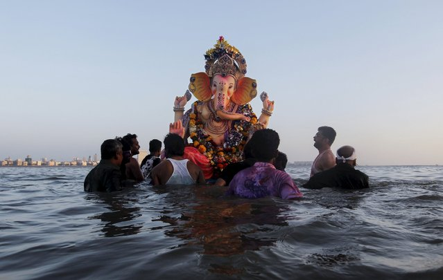 Devotees carry an idol of Hindu elephant god Ganesh, the deity of prosperity, for immersion into the Arabian Sea on the last day of the Ganesh Chaturthi festival in Mumbai, India, September 27, 2015. (Photo by Danish Siddiqui/Reuters)