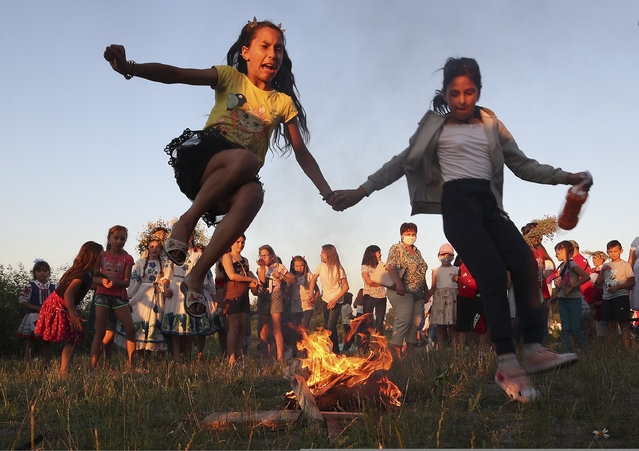 Girls jump over a bonfire during Ivan Kupala Day celebrations held by the Pripyat River in the town of Turau in Gomel Region, Belarus on July 6, 2020. Ivan Kupala Day, also known as Ivana-Kupala or Kupala Night, is a traditional pagan holiday celebrated in eastern Slavic cultures. Various rituals are traditionally performed on Kupala Night, including making flower wreaths, fortune-telling, jumping over bonfires, and burning a wheel-like effigy symbolizing the sun. (Photo by Natalia Fedosenko/TASS)