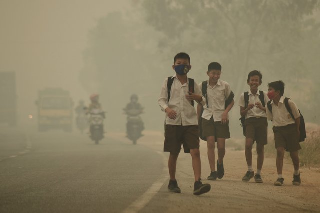 """Students walk along a street as they are released from school to return home earlier due to the haze in Jambi, Indonesia's Jambi province, September 29, 2015 in this picture taken by Antara Foto. Indonesia has sent nearly 21,000 personnel to fight forest fires raging in its northern islands, the disaster management agency said on Tuesday, but smoke cloaks much of the region with pollution readings in the """"very unhealthy"""" region in neighboring Singapore. (Photo by Wahdi Setiawan/Reuters/Antara Foto)"""