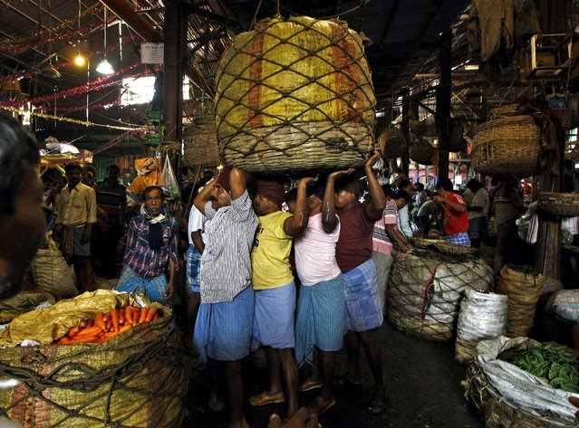 Workers carry a packed basket of vegetables at a wholesale vegetable market in Kolkata, in this February 27, 2015 file photo. (Photo by Rupak De Chowdhuri/Reuters)