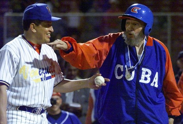 Cuban leader Fidel Castro and Venezuelan President Hugo Chavez joke during a batting session where Chavez pitched to Castro after taking part in a friendly baseball game between their two countries at Barquisimeto's baseball stadium in Venezuela October 29, 2000. Chavez played first base, and Castro managed his national team to an overwhelming victory in the game which was held as part of Castro's state visit to Venezuela. (Photo by Andrew Winning/Reuters)