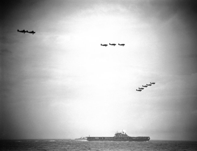 American torpedo planes, returning from raid on Japanese force in the Shortland Islands area of the South Pacific, Ocober 5, 1942, fly in formation as they prepare to land on their carrier. (Photo by AP Photo)