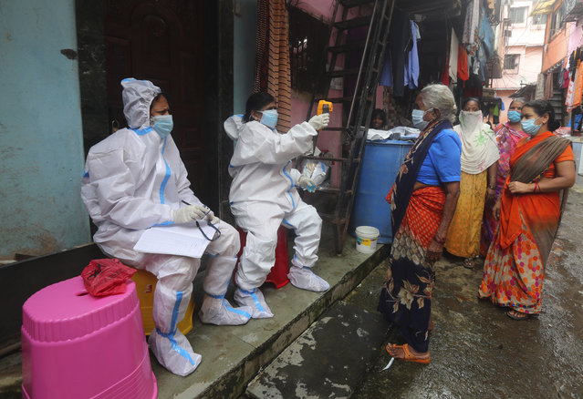 Health workers screen people for COVID-19 symptoms in Dharavi, one of Asia's biggest slums, in Mumbai, India, Tuesday, August 11, 2020. India has the third-highest coronavirus caseload in the world after the United States and Brazil. (Photo by Rafiq Maqbool/AP Photo)
