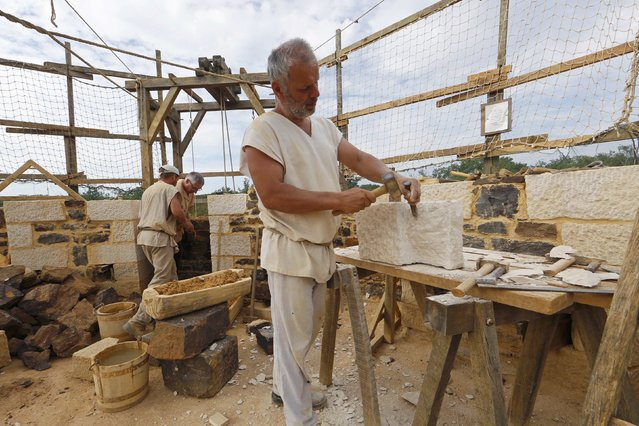Stonecutter and massons work at the construction site of the Chateau de Guedelon near Treigny in the Burgundy region of France, September 13, 2016. (Photo by Jacky Naegelen/Reuters)