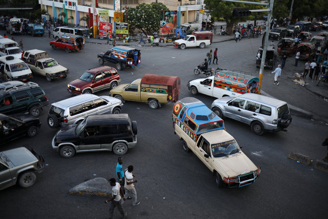 Tap-tap trucks, collective transportation vehicles, and private cars drive through an intersection in Port-au-Prince, Haiti on June 14, 2017. (Photo by Andres Martinez Casares/AP Photo)