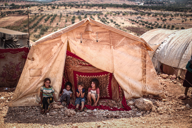 Syrian children sit in front of a tent during hot weather at a refugee camp where displaced Syrians shelter in difficult circumstances in Idlib, Syria on September 01, 2020. Temperatures up to 43 degrees Celsius during the day cause difficulties in tents where most of the women and children live. (Photo by Muhammed Said/Anadolu Agency via Getty Images)