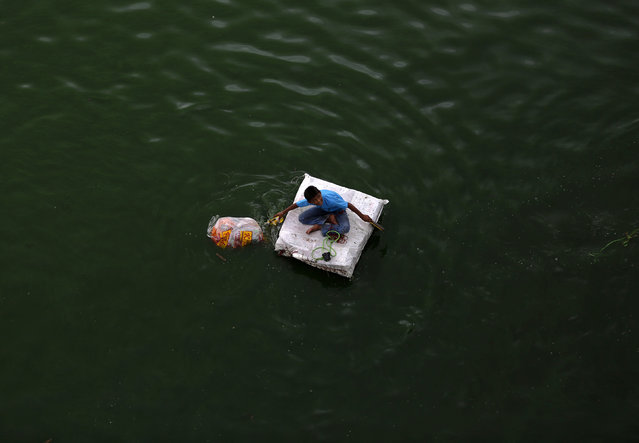 A boy sits on his handmade raft as he collects floating recyclable material in the waters of river Sabarmati in the western Indian city of Ahmedabad July 27, 2014. (Photo by Amit Dave/Reuters)
