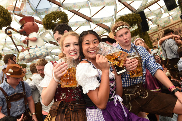 Visitors pose for a picture at the Hofbraeu tent at Oktoberfest in Munich, Germany, 24 September 2016. The 183rd edition of the annual folk and beer festival runs from 17 September to 03 October and is expected to attract once more several millions of visitors from all over the world. (Photo by Felix Hoerhager/EPA)
