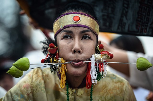 A devotee of the Nine Emperor Gods walks with needles through her face during the annual Phuket Vegetarian Festival in the southern province of Phuket on October 1, 2016. (Photo by Lillian Suwanrumpha/AFP Photo)