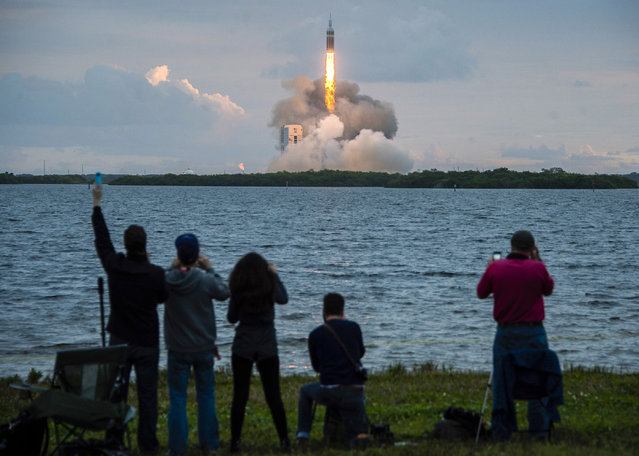 Spectators cheer as the United Launch Alliance Delta 4-Heavy rocket, with NASA's Orion spacecraft mounted atop, lifts off from the Air Force Station, December 5, 2014, in Cape Canaveral, Fla. (Photo by Smiley N. Pool/AP Photo/Houston Chronicle)