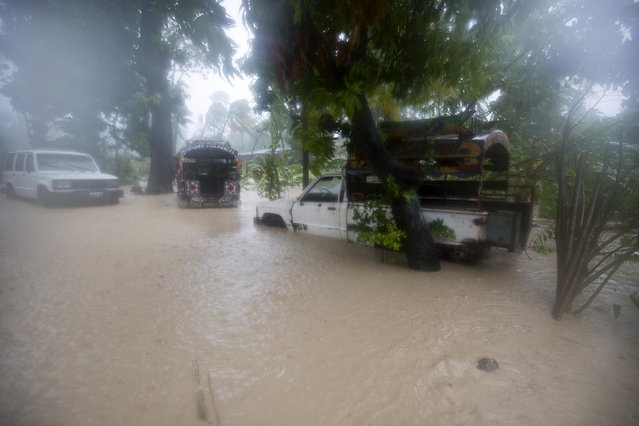 Vehicles sit stranded in flood waters in Leogane, Haiti, Tuesday, October 4, 2016. Matthew slammed into Haiti's southwestern tip with howling, 145 mph winds Tuesday, tearing off roofs in the poor and largely rural area, uprooting trees and leaving rivers bloated and choked with debris. (Photo by Dieu Nalio Chery/AP Photo)