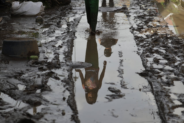 A young resident walks past a mud-covered road after floodwaters caused by Typhoon Goni rose inside their village in Batangas city, Batangas province, south of Manila, Philippines on Monday, November 2, 2020. Super typhoon Goni left wide destruction as it slammed into the eastern Philippines with ferocious winds early Sunday and about a million people have been evacuated in its projected path. (Photo by Aaron Favila/AP Photo)