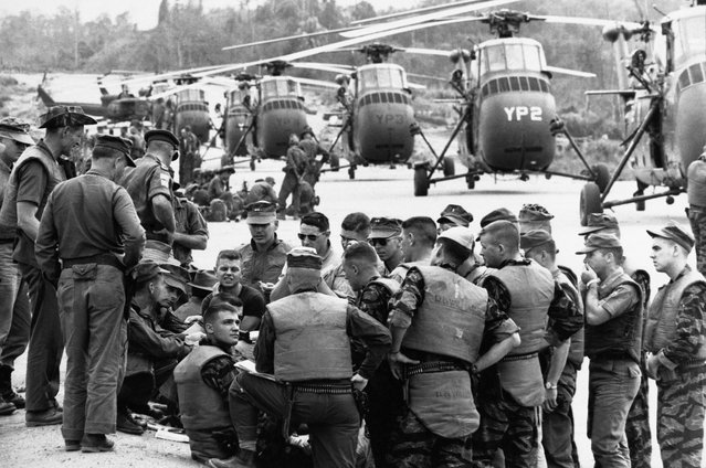 United Sates Marines Helicopter Squadron huddled at Da Nang in 1963 for the final briefing on a March 31, 1965, mission: to airlift a battalion of Vietnamese infantry to an isolated area about 20 miles away. (Photo by Larry Burrows/Time & Life Pictures)