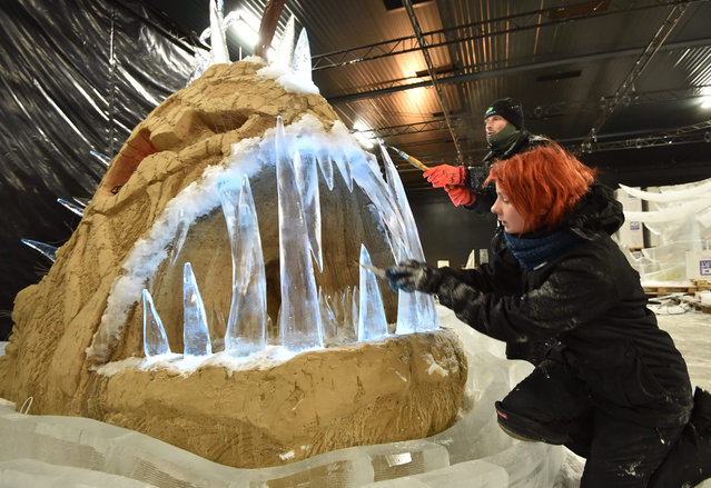 Latvian sculptors Maija Puncule (front) and Karlis Ile work on the sculpture of a giant fish made of ice   and sand in Elstal, Germany, 3 November 2015. According to organisers Germany's largest exhibition of ice sculptures  will open on 28 November 2015. (Photo by Bernd Settnik/EPA)