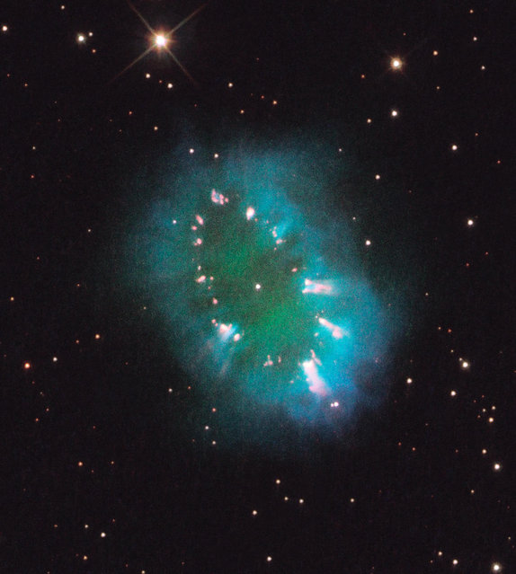 In this image taken July 2, 2011 provided by NASA Thursday August 11, 2011 a giant cosmic necklace glows brightly in this Hubble Space Telescope image. The object, aptly named the Necklace Nebula, is a recently discovered planetary nebula, the glowing remains of an ordinary, Sun-like star. The Necklace Nebula is located 15,000 light-years away in the constellation Sagitta. (Photo by AP Photo/NASA)