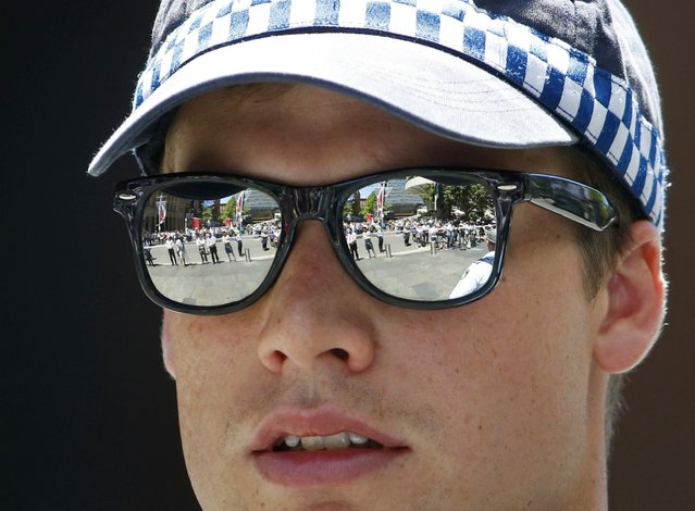 Reporters and other onlookers behind a police cordon are reflected in the glasses of a police officer near Lindt cafe in Martin Place, where hostages are being held, in central Sydney December 15, 2014. (Photo by Jason Reed/Reuters)
