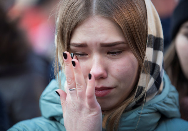 A youth mourns the victims of a shopping mall fire at a makeshift memorial in the Siberian city of Kemerovo, Russia on March 26, 2018. (Photo by Maksim Lisov/Reuters)