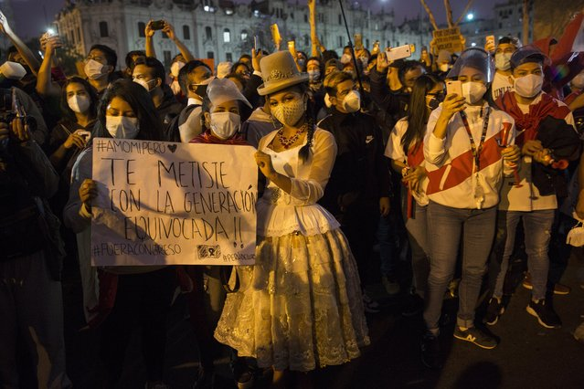 People gather in San Martin square after Peru's new interim President Francisco Sagasti was designated by Congress to lead the nation, in Lima, Peru, Monday, November 16, 2020. (Photo by Rodrigo Abd/AP Photo)