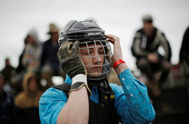 A bull rider dons a helmet before competition at the Deni Ute Muster in Deniliquin, New South Wales, September 30, 2016. (Photo by Jason Reed/Reuters)