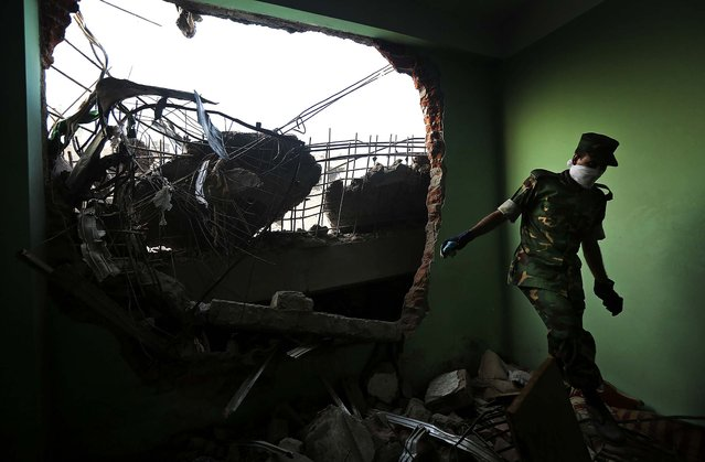A soldier walks through the rubble on Wednesday. (Photo by Kevin Frayer/Associated Press)
