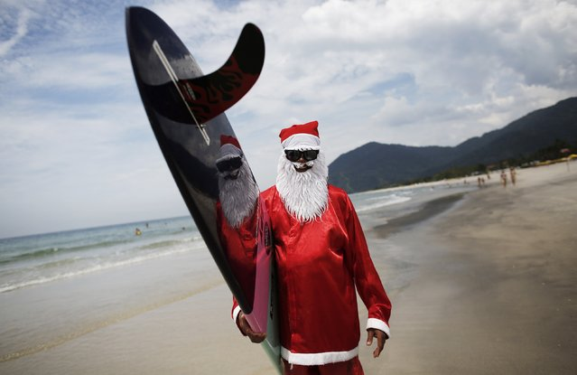 Carlos Bahia, dressed as Santa Claus, poses with his board at the Maresias beach, in the state of Sao Paulo December 9, 2014. (Photo by Nacho Doce/Reuters)