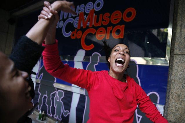 """Madrid Wax Museum employee Noemi Vazquez (L) and her sister Maria celebrate winning a portion of Spain's Christmas Lottery """"El Gordo"""" in Madrid December 22, 2014. (Photo by Juan Medina/Reuters)"""
