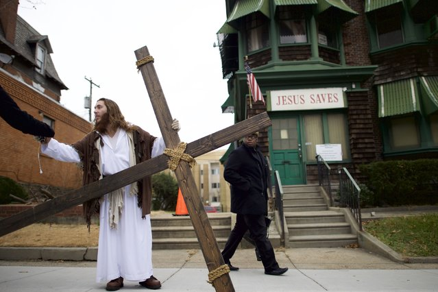 "As a pedestrian looks on, Michael Grant, 28, ""Philly Jesus"", hands a supporter his iPhone and headphones after saying goodbye to a friend, while holding a 12 foot cross which he carried 8 miles through North Philadelphia to LOVE Park in Center City as part of a Christmas walk to spread the true message of the holiday in Philadelphia, Pennsylvania December 20, 2014. (Photo by Mark Makela/Reuters)"