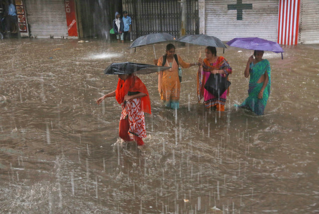 Indian women hold umbrellas and wade through a waterlogged street in the rain in Hyderabad, India, Friday, September 16, 2016. Monsoon season in India begins in June and ends in October. (Photo by Mahesh Kumar A./AP Photo)