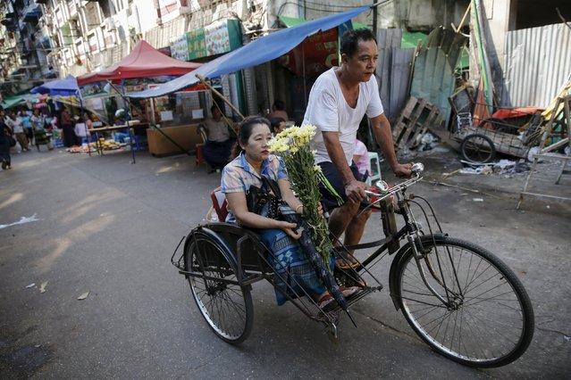 A woman rides a trishaw in downtown Yangon November 7, 2015. (Photo by Jorge Silva/Reuters)