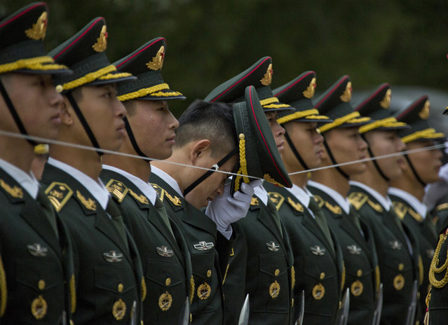 A member of a Chinese honor guard adjusts his cap as they line up with the help of a string before a welcome ceremony for Philippine President Rodrigo Duterte outside the Great Hall of the People in Beijing, China, Thursday, October 20, 2016. (Photo by Ng Han Guan/AP Photo)