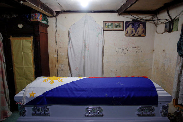 A flag covers the coffin of Rancel Cruz, a police officer killed by an unknown gunman earlier this month, inside his house, before his funeral in Manila, Philippines October 22, 2016. (Photo by Damir Sagolj/Reuters)